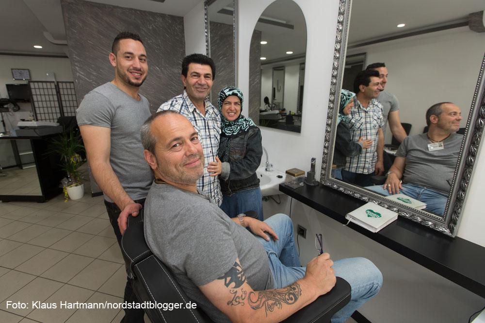 Andreas Horst (vorne) im Friseursalon Anas mit Besitzer-Paar Mariam und Kanem Reefaai und Friseur Danny, v. r.