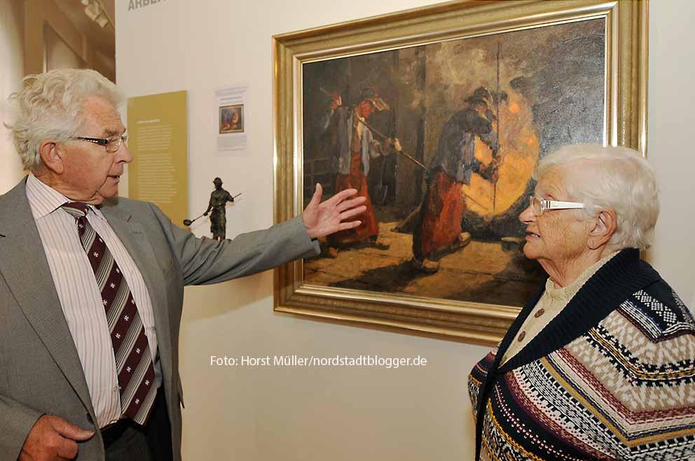 """Horst Klaffke, Hoeschianer im Ruhestand und selbst """"Thomasmann"""", mit Marlies Berndsen an dem Gemälde in der Ausstellung des Hoesch-Museums, das Arbeiter am der Thomasbirne zeigt. Klaffke initierte die Geschichte über die Thomaskerle, die zu Erholung ins Münsterland geschickt wurden. Marlies Berndsen ist die Schwiegertochter Alfred Berndsens, erster Arbeitsdirektor und Erfinder der Erholungsmaßnahme."""