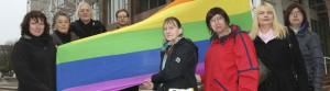 Transidenten-Organisationen Lili Marlene und Transbekannt hissen zusammen mit Unterstützerinnen und Unterstützern Regenbogenfahne am Rathaus