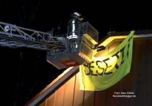 """Die Feuerwehr musste das """"Besetzt""""-Banner mit der Drehleiter entfernen."""