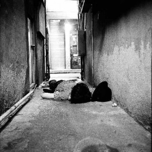 """Eva Teppe: """"Shinjuku Twilight"""", Fotografie, 2008 Die Fotografien wurden von der Künstlerin Eva Teppe in Shinjuku, einem Stadtteil von Tokio, über einen Zeitraum von einigen Wochen immer um 5 Uhr morgens aufgenommen. Zu dieser Zeit entsteht eine bizarre Atmosphäre in dieser Gegend: leblos scheinende, erschöpfte Körper liegen in den Straßen während gleichzeitig tausende Japaner ihr Ta- geswerk beginnen."""