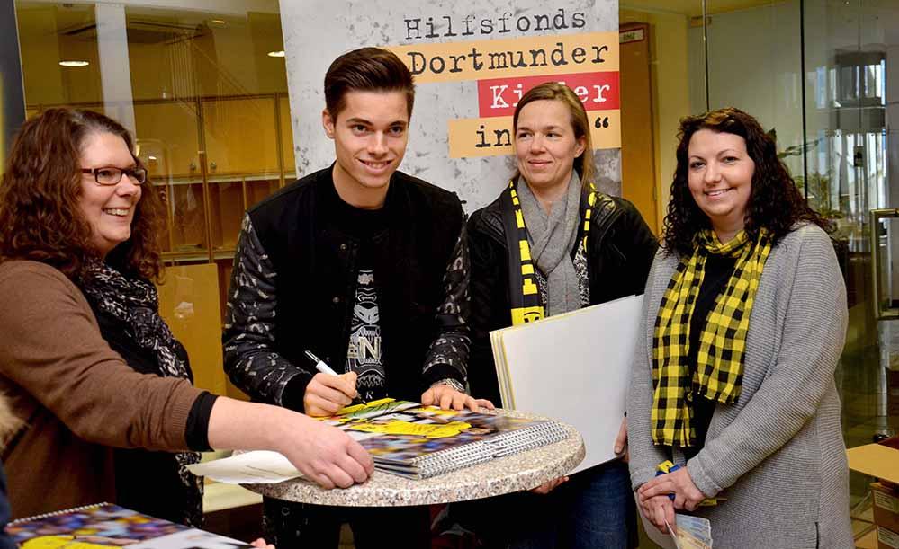 """BVB-Mittelfeldspieler Julian Weigl unterschrieb im Katholischen Centrum 321 Posterkalender zugunsten des Hilfsfonds' """"Dortmunder Kinder in Not"""", hier mit Kerstin Vogler, Sabine Omlin und Vinka Slisko (v.l.)."""