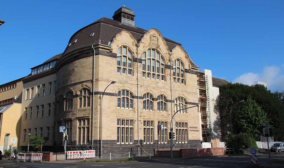 Denkmalgeschützte Fassade in neuem Glanz: Natursteinfassade und Holzfenster des Helmholtz-Gymnasiums wurden in Handarbeit saniert.