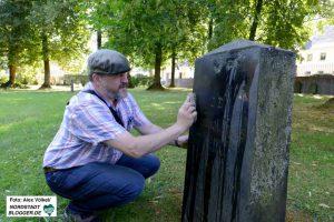 Heimatforscher Klaus Winter reinigt einen der Steine in Hörde.