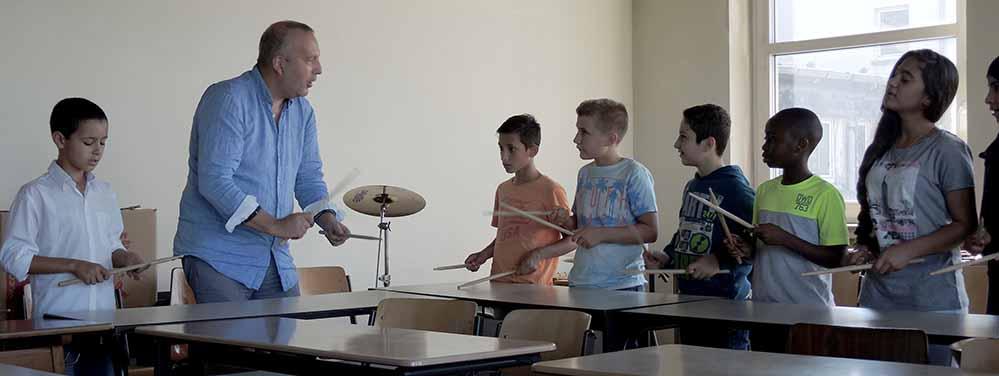 Die Schülerinnen und Schüler der Willkommensklasse 1 an der Anne-Frank-Gesamtschule beweisen in einer Trommel-AG ihr Rhythmusgefühl.