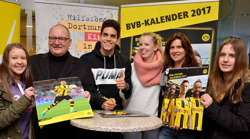BVB-Abwehrspieler Marc Bartra (3.v.r) unterschrieb im Katholischen Centrum den BVB-Posterkalender. Hier mit Propst Andreas Coersmeier (2.v.r.) sowie jungen Fans und Mitarbeiterinnen vom Katholischen Sozialen Dienst SKM. Foto: pdp