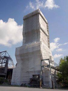 Unter der Plane finden die Arbeiten an der Holzkonstruktion statt.