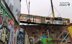 Bus wird am Junkyard über die Mauer gehoben