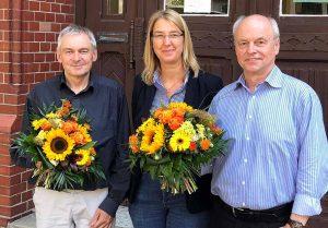 Abschied und Neustart am Schulmuseum: Rüdiger Wulf geht, Michael Dückershoff (links) übernimmt. Blumen gabs von Dr. Dr. Elke Möllmann. Foto: Joachim vom Brocke
