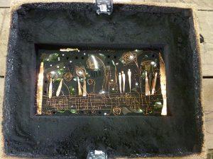 Eine mit Kupferdraht und Glasscherben ausgelegte Sandgussform.