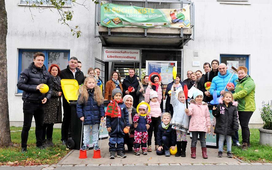 VertreterInnen der Dortmunder Wohnungsgesellschaften und der Kinder- und Jugendeinrichtungen in der Nordstadt bei der Übergabe der Spieletonnen in der Libellensiedlung. Foto: Sascha Fijneman