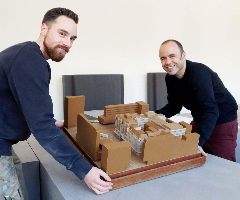 Kleines Gartenzimmer: Modellbauer Felix Florian und Christos Stremmenos heben ein Modell in den dafür vorgesehenen Ausschnitt.