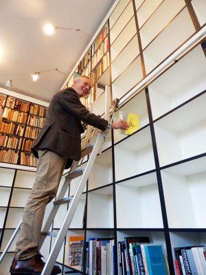 Prof. Wolfgang Sonne bugsiert den neuen Katalog zur ersten Ausstellung im Baukunstarchiv ins Regal der neuen Bibliothek. 8000 Bücher haben hier Platz.
