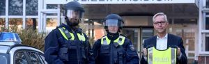 Die Polizeikommissare Ann-Kathrin Ossenkopp und Nils Jäger präsentieren mit Polizeipräsident Gregor Lange die neue Ausrüstung.