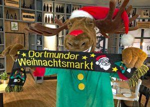 """Erstmals gibt es Schals zum Weihnachtsmarkt. Elch """"Siggi"""" präsentiert sie in der schwarz-gelben Version, es gibt aber auch einen Schal in rot-weiß."""