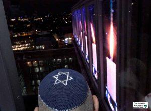 Ein Mitglied der jüdischen Gemeinde blickt fasziniert auf die Kerzen auf dem Dortmunder U.
