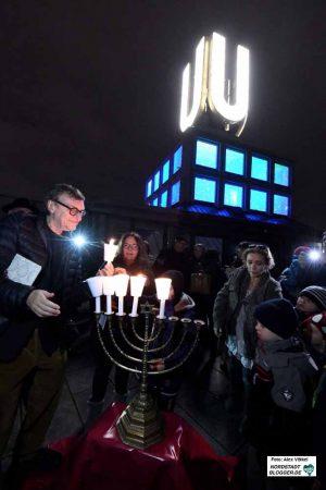 """Prof. Adolf Winkelmann brachte den Chanukka-Leuchter auf seine """"Fliegenden Bilder"""" und entzündete auch eine Kerze."""