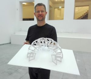 Peter Dahmen mit aufgeklappter Papierskulptur