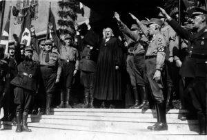 Eröffnung der Nationalsynode in Wittenberg. Landesbischof Ludwig Müller (der spätere Reichsbischof) beim Heilruf mit dem faschistischen Gruß auf Adolf Hitler. 1933 Von Bundesarchiv, Bild 183-H25547 / CC-BY-SA 3.0,