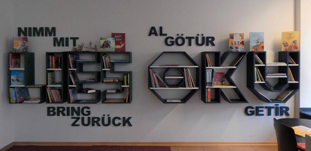 """Die Bücherregale bilden die Worte """"Lies"""" und dessen türkische Übersetzung """"Oku"""". Drum herum steht noch """"Nimm mit"""", """"Bring zurück"""" und die türkischen Pendants """"Al götür"""", """"Getir""""."""
