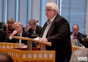 Heiner Garbe (AfD) rät in der Haushaltsdebatte dem Kämmerer Jörg Stüdemann (Im Hintergrund) sinngemäß, den Gürtel enger zu schnallen und strukturelle Einsparungen vorzunehmen.