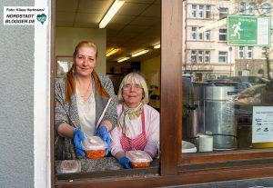Kana-Suppenküche in Zeiten der Corona-Krise. Katja und Lisa reichen am Fenster Suppe an hunrige Menschen. Die Räumlichkeiten selbst sind geschlossen