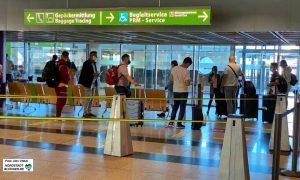 Fluggäste mit Masken beim Check-Inn am Dortmunder Flughafen