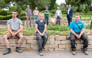Auf dem Gruppenbild im Vordergrund drei am Projekt beteiligte Auszubildende. In der Reihe dahinter sind Mitarbeitende der Friedhöfe Dortmund zu sehen, die Winzerin Tina Krachten (3.v.r.) und Stadtrat Arnulf Rybicki (1.v.r.).