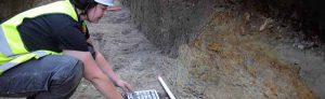 Deutlich erkennbar, die dunkelgrauen Schichten der Grabenverfüllung im Profil und im Planum des Leitungsgrabens. Die Sohle des Wassergrabens wurde bei den Arbeiten nicht erreicht. Denn ausgegraben wird immer nur so viel wie unbedingt durch die Baumaßnahme erforderlich. (Fotos: Stadt Dortmund / LQ-Archäologie