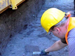 """Damals Abfall, heute wertvolle Hilfe. Was aussieht wie braune unförmige Flecken in der Grabenverfüllung ist in Wahrheit Holz, das beim Verfüllen mit in den Graben gelangt war. Als Füllmaterial hatte man alles verwendet was in der Nähe verfügbar war und nicht mehr genutzt wurde. Heute kann man mit der sogenannten """"14C-Methode"""" das Alter des Holzes bestimmen, um so weitere Anhaltspunkte zum Alter des Grabens zu erhalten."""