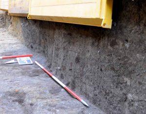 Der ehemals wasserführende Graben hatte ein v-förmiges Profil. Um die notwendige Tiefe zu erreichen, hatte man tief in den natürlichen Lehmboden gegraben. Dank der dunkelgrauen Grabenverfüllung lässt sich der ehemalige Graben hervorragend von dem gelb-grauen Lehmboden abgrenzen.
