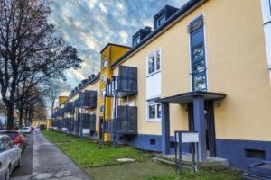 Neue Balkone und frische Farben für DOGEWO21-Häuser in Dorstfeld  Am Hartweg in Dorstfeld hat DOGEWO21 umfangreiche Instandhaltungs- und Modernisierungsarbeiten abgeschlossen. So erhielten die Häuser Am Hartweg erstmals 1,5x3 Meter große Anstellbalkone.Im Zuge der Maßnahme wurden die Fenster im Balkonbereich erneuert und Balkontüren eingebaut. Die Fassaden der rund 90 Jahre alten Häuser Am Hartweg 139-149 wurden saniert und haben einen freundlichen, neuen Farbanstrich erhalten. Weiter wurden Haustüren und Treppenhausfenster ausgetauscht, Vordächer montiert, die Treppenhäuser gestrichen und mit neuer Elektrik ausgestattet. Für zusätzliche Sicherheit sorgen neue Außenbeleuchtungen sowie Gegensprechanlagen. Die Gesamtkosten für die Maßnahme liegen bei knapp 360.000 Euro. Die Wiederherstellung der Außenanlagen erfolgt zum Frühjahr 2021. Nachdem Anfang 2019 bereits die benachbarten Häuser Am Täufling umfangreich saniert und mit Balkonen ausgestattet wurden, wird DOGEWO21 die Instandhaltung der Dorstfelder Siedlung im kommenden Jahr mit weiteren Maßnahmen fortsetzen. Info: Mit über 16.300 Wohnungen zählt DOGEWO21 zu den größten Vermietern in Dortmund. 2020 investiert das Unternehmen insgesamt 34,5 Millionen Euro in Neubauprojekte, Modernisierung und Instandhaltung. DOGEWO21 baut allein in diesem Jahr fast 190 neue Balkone an ihre Häuser in Eving, Huckarde und Dorstfeld an. Bild: DOGEWO21