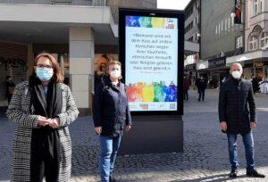 Anja Butschkau und Mirja Düwel von der AWO präsentiertenmit Cristian Kohut (Wall) die virtuellen Plakate in der City.