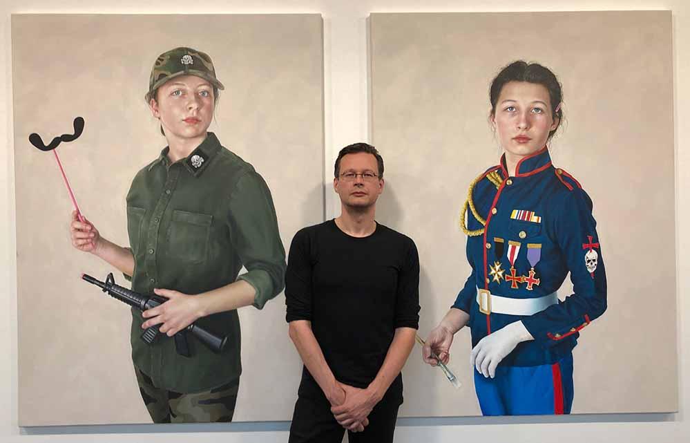 """Der Künstler René Schoemakers in der Ausstellung vor dem Diptychon """"Karl-Heinz (Mummenschanz)"""" (li) und """"Anders (Mummenschanz)"""" (2019). Fotos: Katrin Pinetzki"""