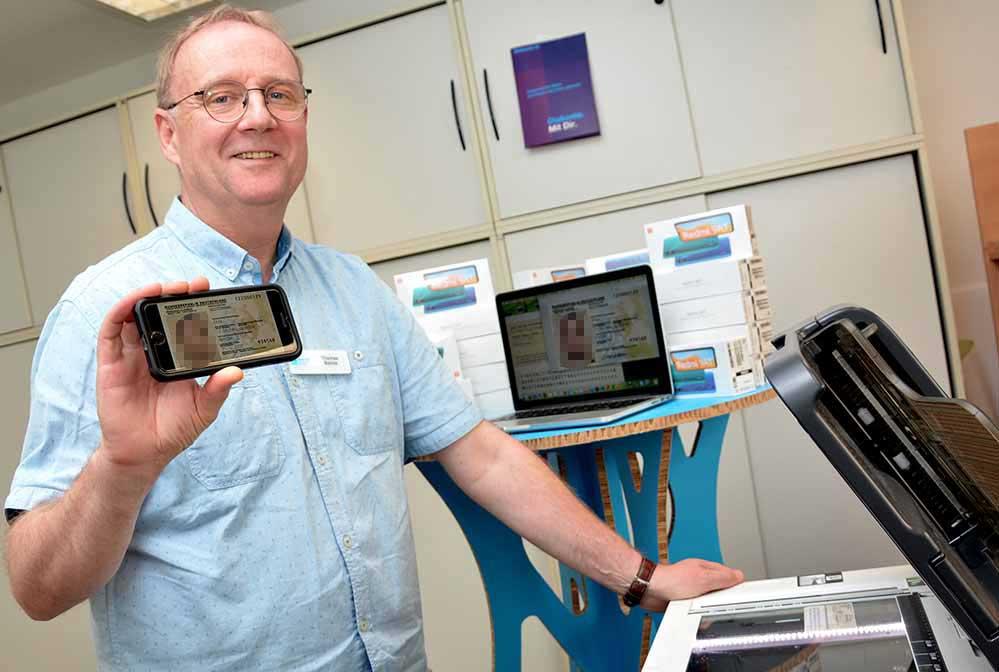 Thomas Bohne von der Wohnungslosenhilfe der Diakonie in Dortmund bei der Digitalisierung von persönlichen Dokumenten von Menschen, die sich an die Diakonie wenden.